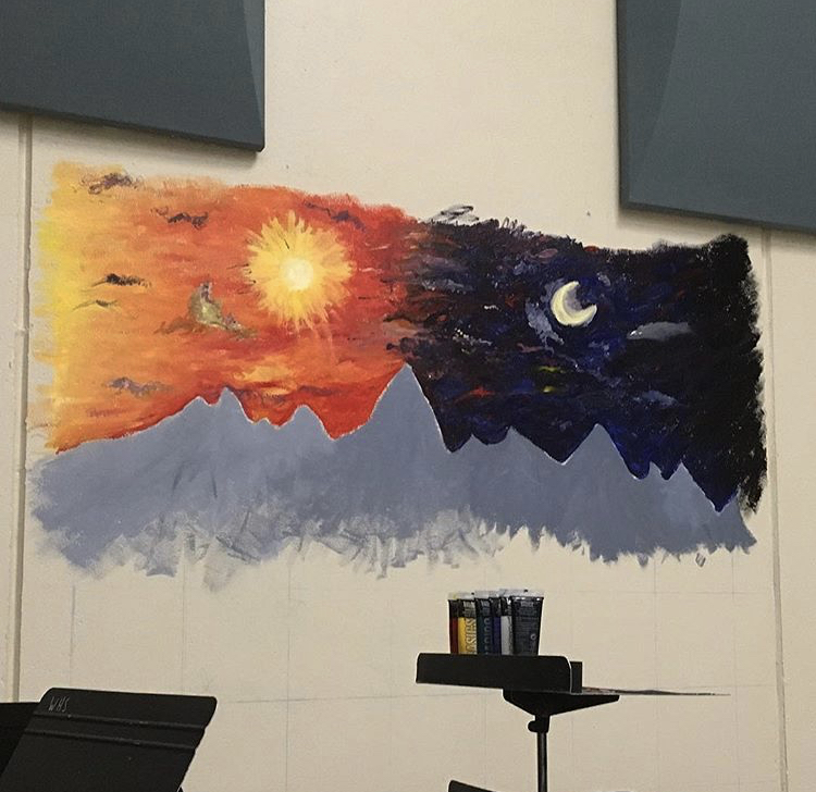 This mural, depicting mountains under a sunset and a night sky, is half-complete, with plans to finish it this fall.